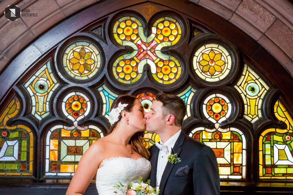 Bride and groom in front of stained glass
